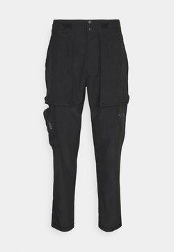 Puma - TRAIN FIRST MILE - Spodnie materiałowe - black